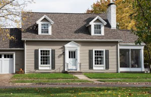 Gray Cape Cod style house with screened-in side porch.